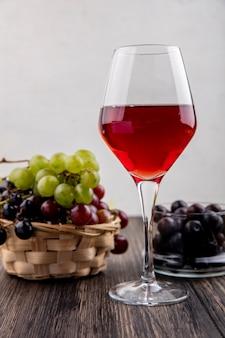 Zijaanzicht van zwarte druivensap in wijnglas met druiven in de mand en in kom op houten oppervlak en witte achtergrond