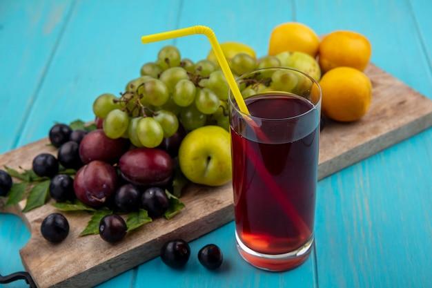 Zijaanzicht van zwarte druivensap met drinkbuis in glas en nectacots pluots druif op snijplank op blauwe achtergrond