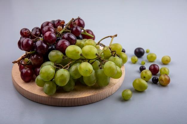 Zijaanzicht van zwarte en witte druiven op snijplank en op grijze achtergrond