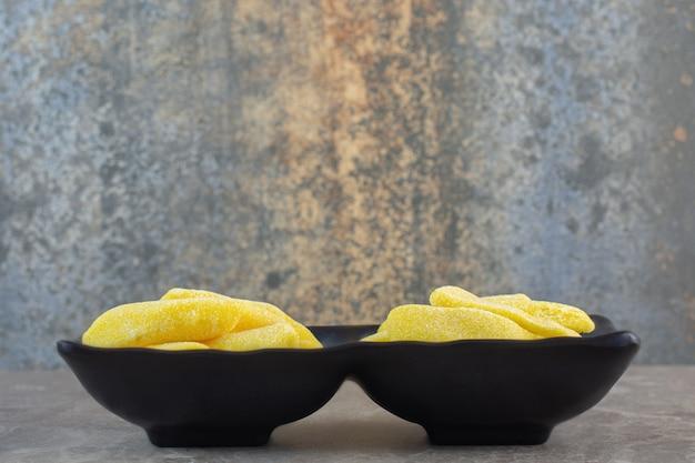 Zijaanzicht van zwarte kom vol met gele zoete snoepjes.