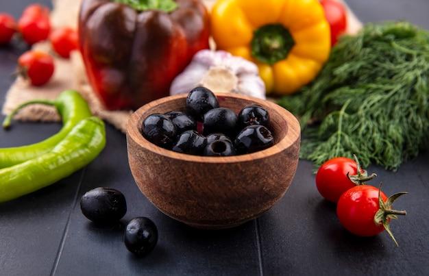 Zijaanzicht van zwarte olijven in kom met peper knoflook bol tomaat en bosje dille rond op zwarte ondergrond