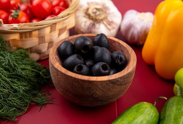 Zijaanzicht van zwarte olijven in kom met tomaten knoflook dille peper komkommer op rode ondergrond