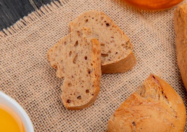 Zijaanzicht van zwarte stokbroodplakken met gesmolten boter op jute