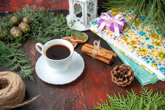 Zijaanzicht van zwarte thee, kaneellimoenen, een bal van touwspartakken en boeken op een donkere achtergrond