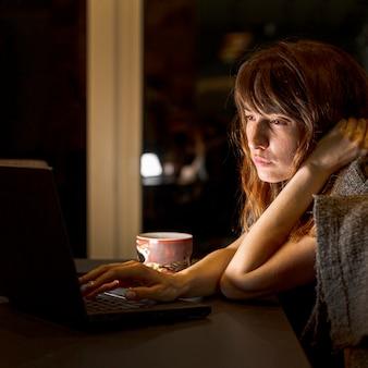 Zijaanzicht vermoeide vrouw met laptop binnenshuis