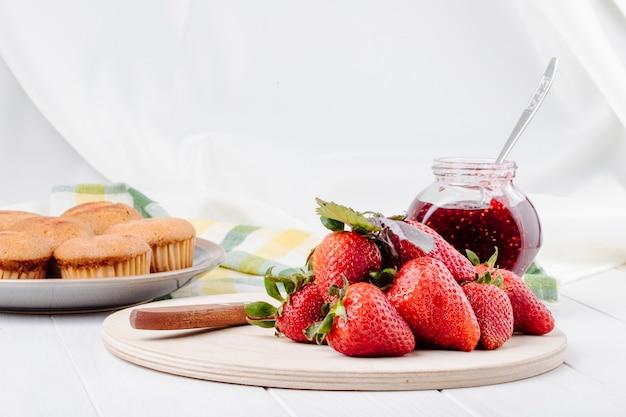 Zijaanzicht verse aardbeien cupcakes en aardbeienjam op witte achtergrond