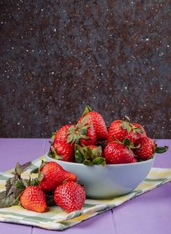 Zijaanzicht verse aardbeien met basilicum op paarse en zwarte achtergrond