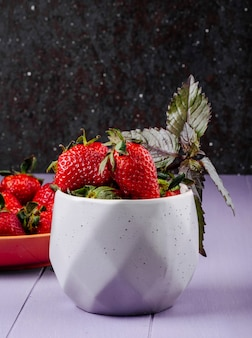 Zijaanzicht verse aardbeien op zwarte en paarse achtergrond