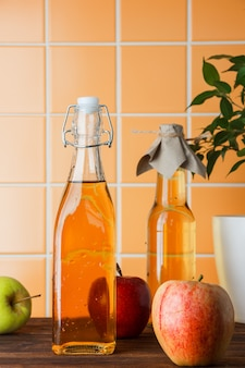 Zijaanzicht verse appel met appelsap op oranje tegelachtergrond. verticaal