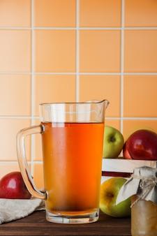 Zijaanzicht verse appelen in doos met appelsap op oranje tegelachtergrond. verticale ruimte voor tekst