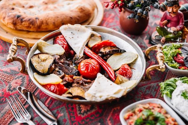 Zijaanzicht vlees salie met pitabroodje tomaten en salades op tafel