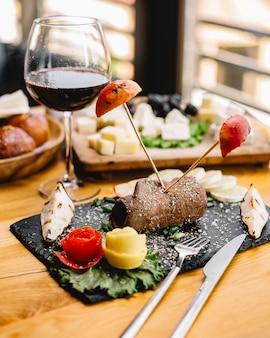 Zijaanzicht vleesrol met gegrilde appels en peren met een glas rode wijn