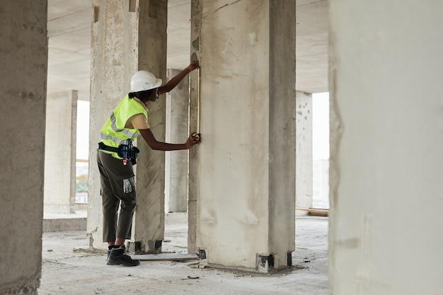 Zijaanzicht volledig portret van jonge afro-amerikaanse vrouw die werkt op de kopieerruimte van de bouwplaats