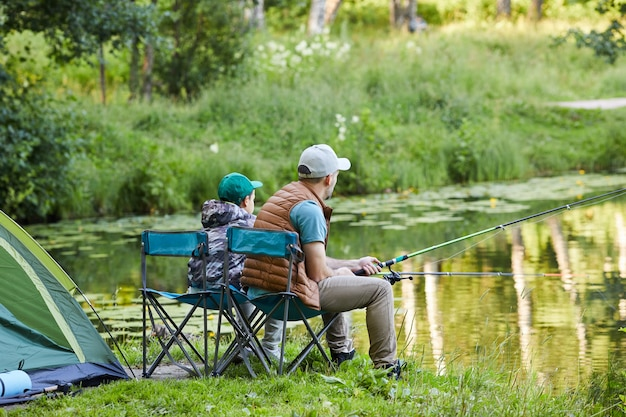 Zijaanzicht volledige lengte portret van liefdevolle vader en zoon samen vissen aan het meer tijdens kampeertrip in de natuur, kopie ruimte