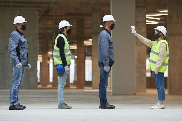 Zijaanzicht volledige lengte van vrouwelijke supervisor temperatuur meten van werknemers met contactloze thermometer op bouwplaats, coronavirus veiligheidsmaatregelen