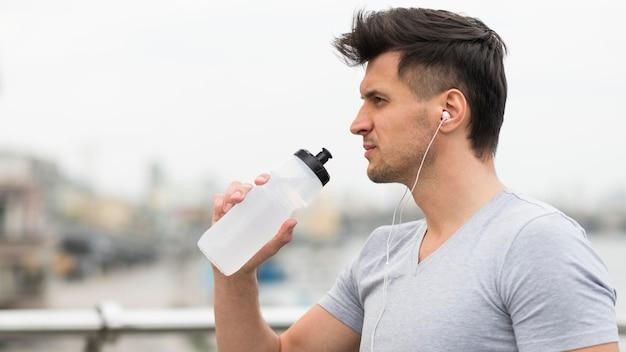 Zijaanzicht volwassen mannelijk drinkwater