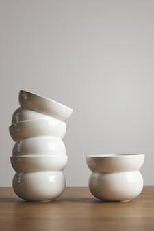 Zijaanzicht vormige lege witte eenvoudige keramische koffiekopjes in pyramide op dikke houten tafel geïsoleerd