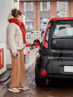 Zijaanzicht vrouw bij benzinestation