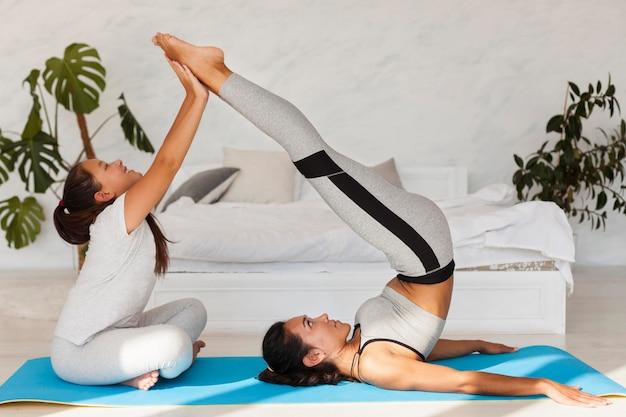 Zijaanzicht vrouw die zich uitstrekt op yoga mat