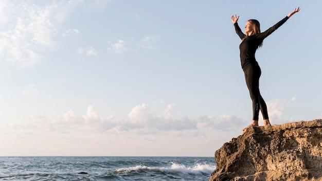 Zijaanzicht vrouw genieten van het uitzicht op de kust met kopie ruimte