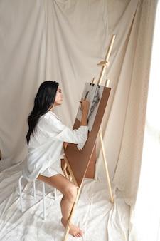 Zijaanzicht vrouw kunstenaar in wit shirt tekening foto met potlood (vrouw levensstijl concept)