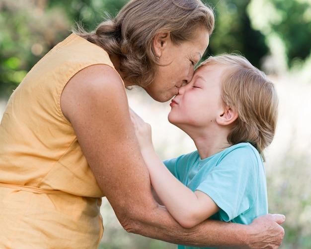 Zijaanzicht vrouw kussen kleinzoon
