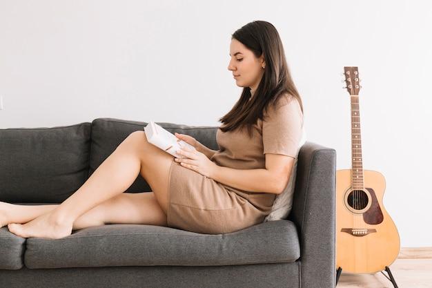 Zijaanzicht vrouw leesboek op de bank