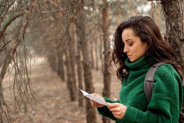 Zijaanzicht vrouw leest kaart