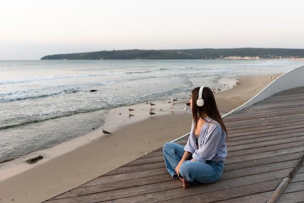 Zijaanzicht vrouw luisteren naar muziek naast de zee