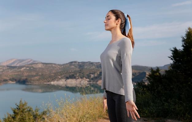 Zijaanzicht vrouw mediteren in de natuur