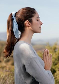 Zijaanzicht vrouw mediteren in de natuur Gratis Foto