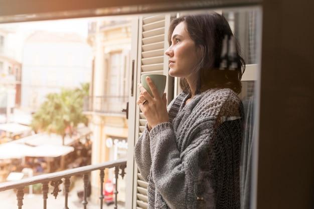 Zijaanzicht vrouw met een kopje koffie