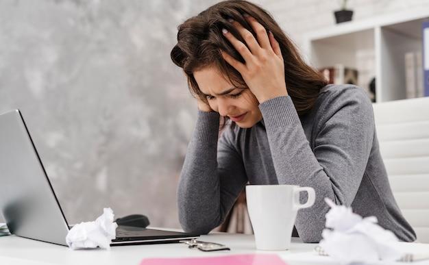 Zijaanzicht vrouw met hoofdpijn tijdens het werken vanuit huis