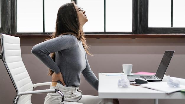 Zijaanzicht vrouw met rugpijn tijdens het werken vanuit huis