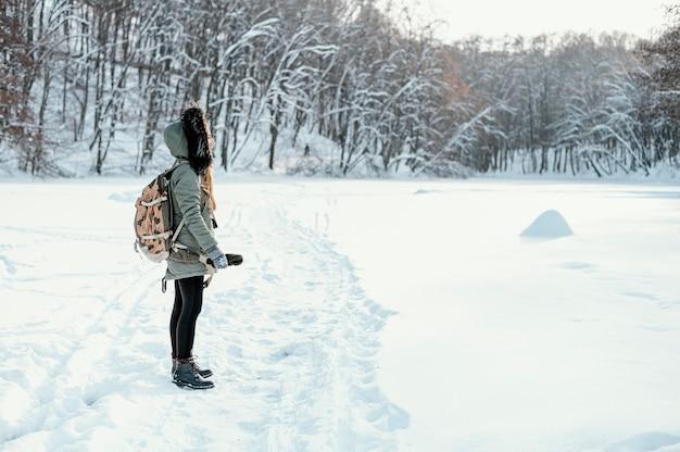 Zijaanzicht vrouw met rugzak op winterdag