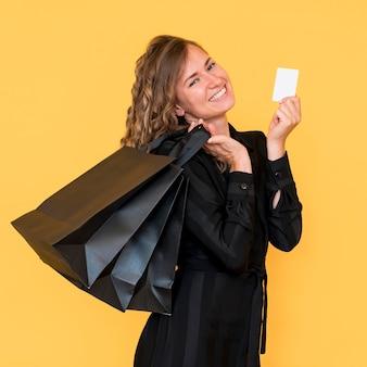 Zijaanzicht vrouw met zwarte boodschappentassen