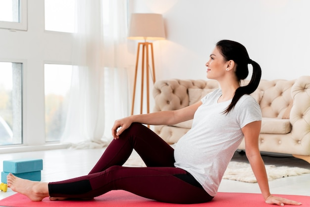 Zijaanzicht vrouw ontspannen na het sporten tijdens de zwangerschap