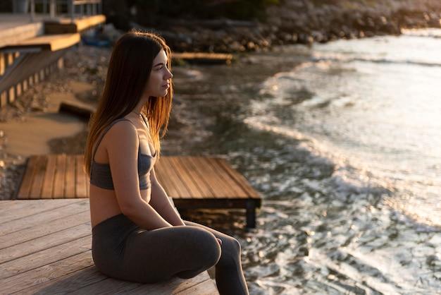 Zijaanzicht vrouw ontspannen op het strand