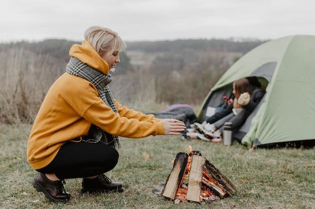 Zijaanzicht vrouw opwarming van de aarde bij kampvuur