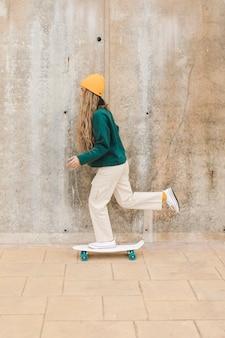 Zijaanzicht vrouw rijden skateboard buiten