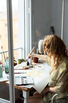 Zijaanzicht vrouw zitten en schilderen
