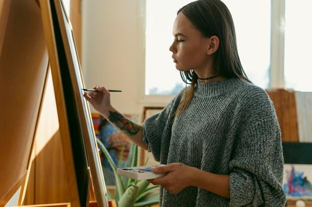 Zijaanzicht vrouwelijk schilderij en haar werk