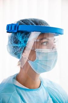 Zijaanzicht vrouwelijke arts in beschermende kleding wegkijken