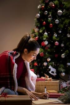 Zijaanzicht vrouwelijke het schrijven brief voor de kerstman