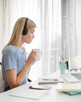 Zijaanzicht vrouwelijke student die haar ochtendkoffie drinkt