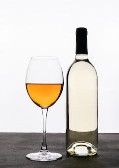 Zijaanzicht witte wijn met glas op witte verticaal