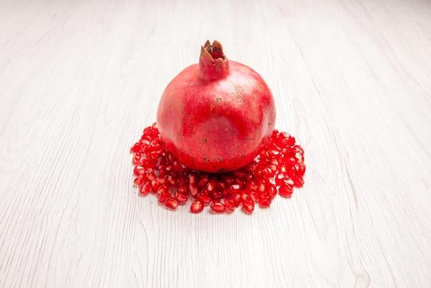 Zijaanzicht zaden van granaatappel zaden van granaatappel rond rijpe granaatappel op de witte tafel