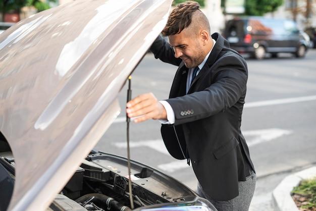 Zijaanzicht zakenman kijkt onder de motorkap