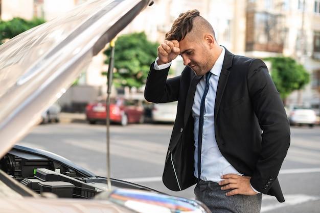 Zijaanzicht zakenman probeert zijn auto te repareren