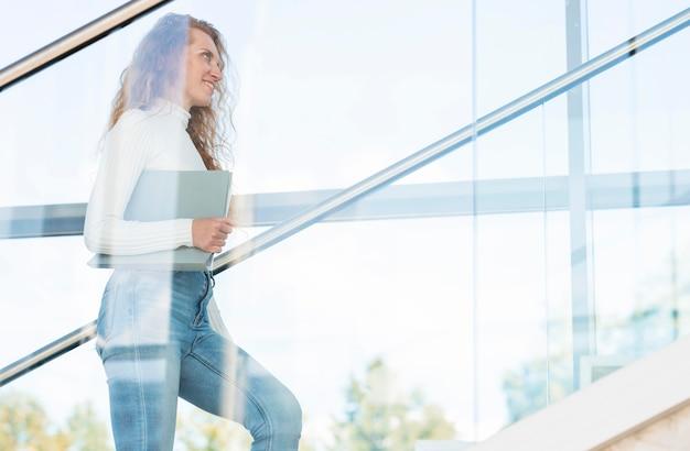 Zijaanzicht zakenvrouw de trap oplopen